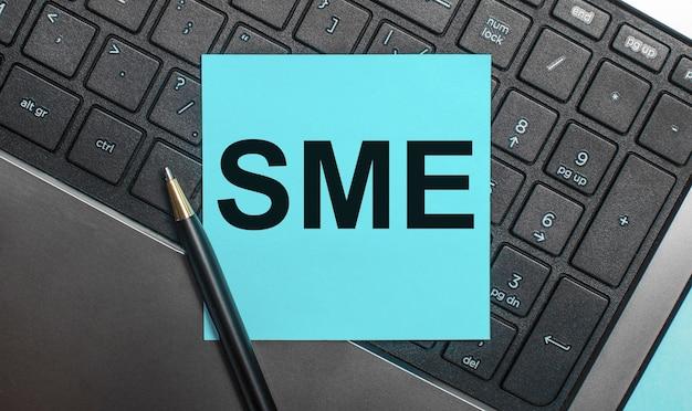 На клавиатуре компьютера есть ручка и синяя наклейка с текстом sme subject matter expert. плоская планировка.