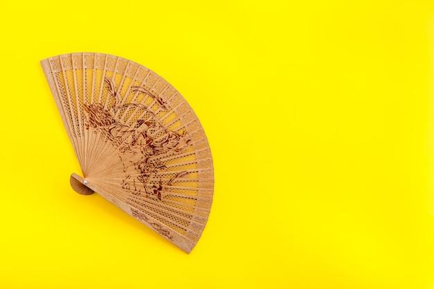 Концепция бамбукового вентилятора на желтом фоне