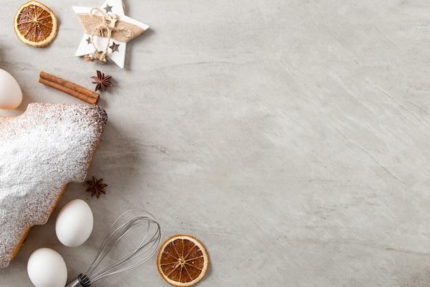 Концепция рождественской открытки. домашняя выпечка, ингредиенты, печенье в форме елки и украшения на каменном фоне. вид сверху, плоская планировка.