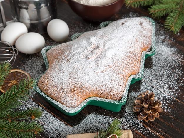Концепция рождественской открытки. домашняя выпечка, ингредиенты, печенье в форме елки, подарки, еловые ветки и украшения. вид сверху, плоская планировка.