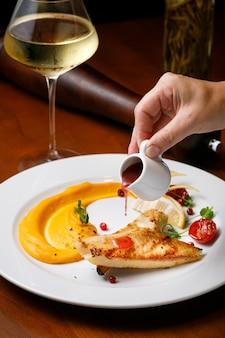 レストランの美しいヨーロッパ料理のコンセプト。ステーキの切り身の魚のフライとベリーソースの白皿に白ワインを添えて揚げたもの。高品質の写真。