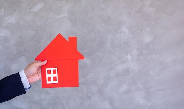 家または売り家と手に赤い家を買うビジネスパーソンの概念。新規採用バイヤーのための家の計画方法に関するアドバイス