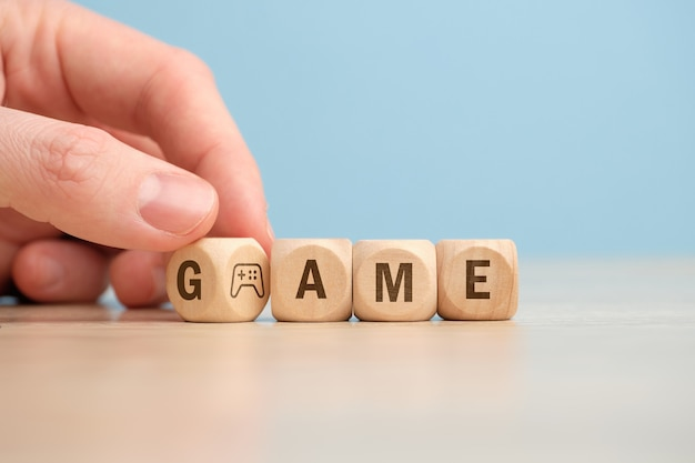 나무 큐브에 조이스틱 아이콘이있는 게임 선택의 개념은 손으로 뒤집습니다.