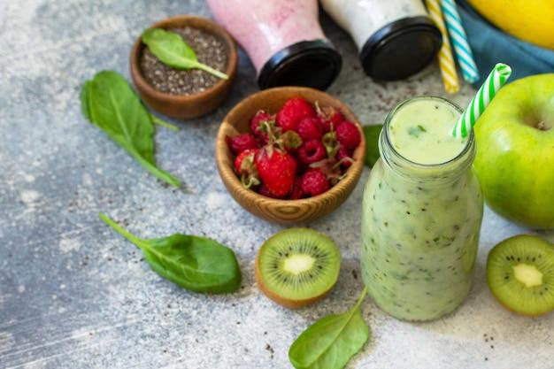 Концепция здорового питания. детокс смузи микс. зеленые смузи овощные и фруктовые смузи на каменной бетонной столешнице. копировать пространство