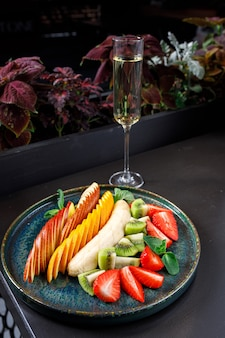 Концепция здорового питания. на тарелке фрукты и ягоды - яблоко, апельсин, банан, киви, клубника, мята.
