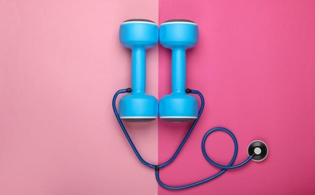 Концепция здорового образа жизни и заботы о здоровье. гантель со стетоскопом на розовом пастельном фоне. вид сверху