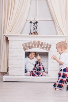 Концепция здорового образа жизни, защита детей, домашний интерьер - это подростки, играющие вместе. счастливые дети: братья у камина