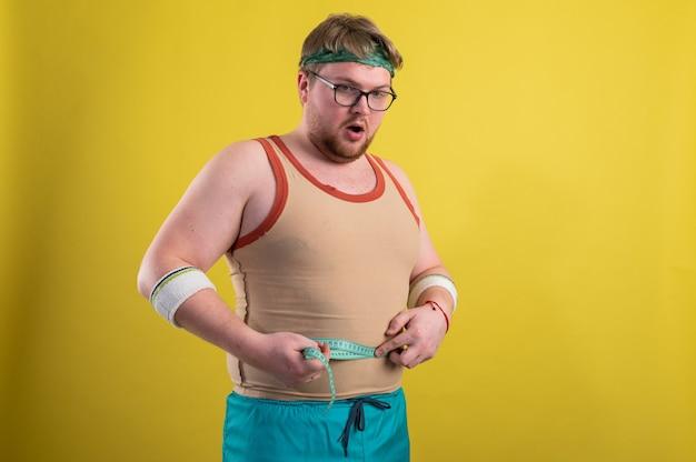 건강한 라이프 스타일의 개념. 과체중 남자는 신체 매개 변수를 측정합니다.