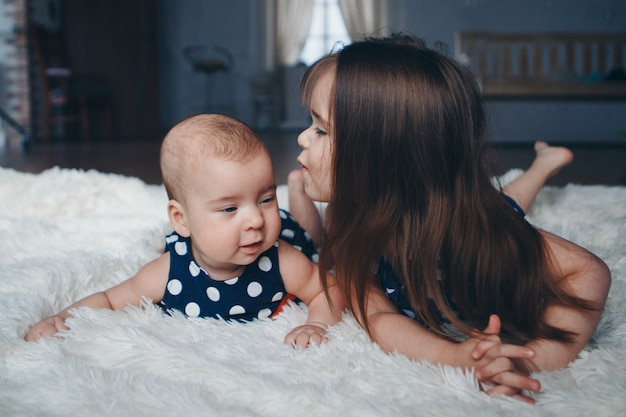 Концепция здорового образа жизни, защита детей, шоппинг - подросток с новорожденным ребенком, играющим вместе. счастливые дети: сестры лежат на полу
