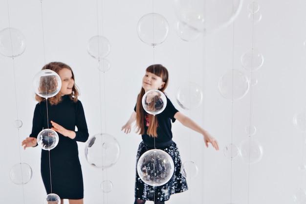 Концепция здорового образа жизни, защита детей, шоппинг - подростки играют вместе. счастливые дети: сестры на белом фоне
