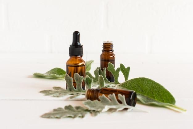 천연 유기농 에센셜 오일의 개념. 흰색 벽돌 벽의 배경에 화장품 천연 치료제가 있는 두 병.