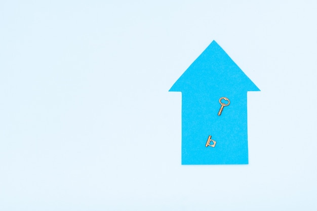 새 집, 모기지, 대출의 개념. 꿈의 집 개념입니다. 파란색 종이 집 모델과 파스텔 배경의 열쇠, 조롱, 복사 공간, 위쪽 전망
