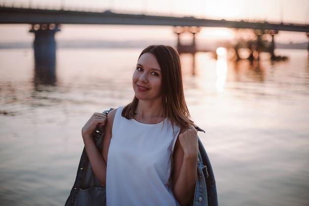Концепция романтического свидания кавказская женщина в белом платье накинула джинсовую куртку поверх своего шоу ...