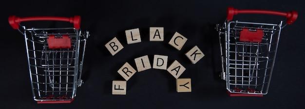 Концепция продажи в магазине кубиков с надписью черная пятница и тележка супермаркета на черном фоне
