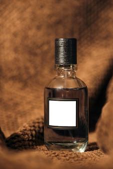 ダークブラウンの織り目加工の生地を背景にした、男性の香水の厳格で残忍で豊かな香りのコンセプト。