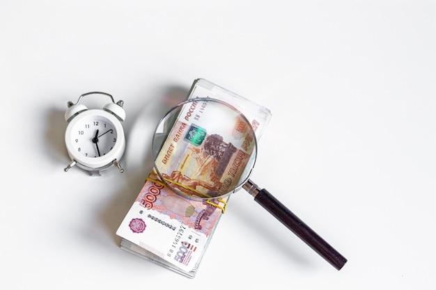 Концепция накопления и вложения денег пятитысячными рублевыми купюрами через увеличительное стекло.