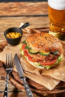 アメリカのファーストフードの概念。ジューシーなアメリカンバーガー。ビーフパティ2枚と、木製の背景のガラステーブルにダークビールを添えています。コピースペース