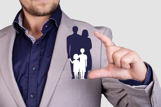 クライアントである家族のアイコンを保護およびサポートする保険会社のコンセプト。ビジネスマンの手によって保護されています。高品質の写真