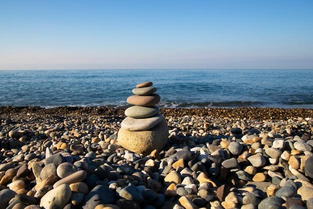 バランスと調和の概念。自然のビーチの石。小石のビーチにある石のピラミッド、背景には夜明けの海と空のぼやけた背景
