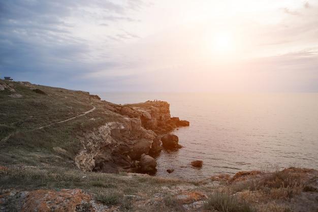 보트 타기, 레크리에이션, 여행의 개념 - 바다, 바다, 산, 하늘, 돌 해안에 푸른 물이 튀었습니다. 복사 공간