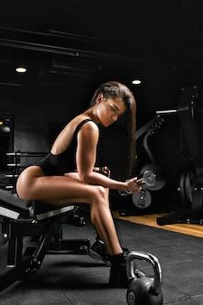 ボディービルのコンセプト、美しい体の構造、ジム。アスリートの女の子は腕二頭筋の運動をします。美しい体。