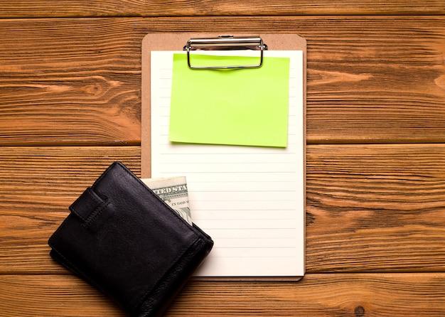 Понятие о бизнесе и финансах. бланк с чистым листом бумаги и кошелек с деньгами на деревянном столе.