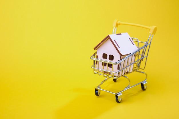 Концепция покупки дома. модель дома в корзине на желтом фоне