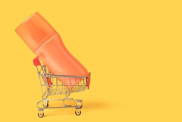 Концепция покупки и продажи косметического крема и лосьона для загара. корзина на желтом фоне. крупный план.