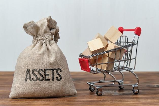 Концепция покупки любых активов. сумка для денег рядом с тележкой для покупок