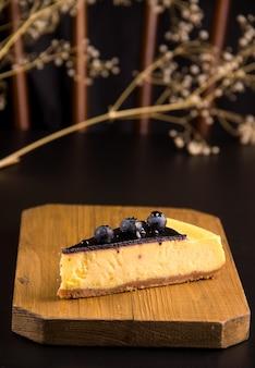 케이크의 개념입니다. 검은색 바탕에 블루베리와 카라멜을 넣은 치즈 케이크