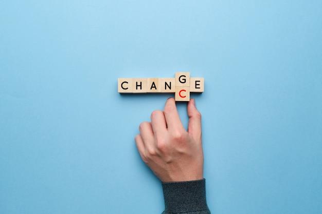 変化とチャンスの概念。手は黄色の背景に文字をピックアップします。
