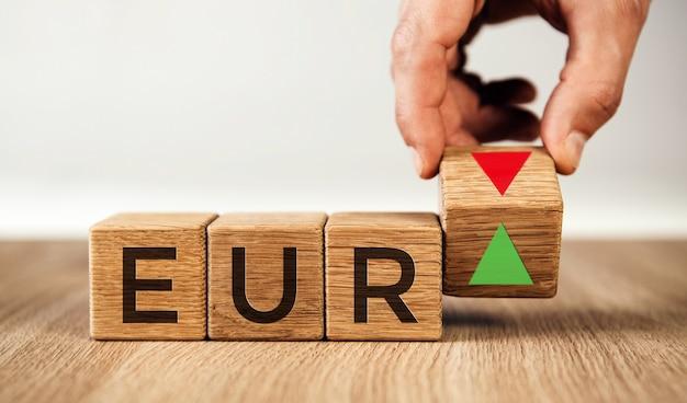 Концепция изменения стоимости евро. рука поворачивает кубик и меняет направление стрелки.