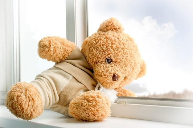 多階建ての建物の開いた窓での子供の安全の概念。子供のおもちゃのクマは窓にあります。