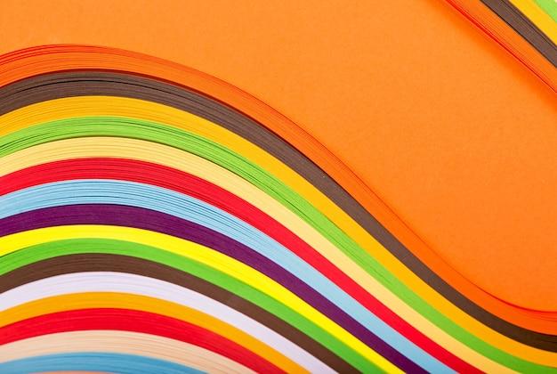 オレンジ色の表面に子供の創造性、趣味、レクリエーションカールレインボーストリップ紙の概念