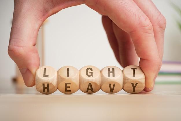 選択の概念は、木製の立方体で軽くて重い、手でひっくり返します。