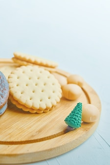 Концепция рождественского и новогоднего печенья и конфет на деревянном подносе маленький зеленый рождественский т ...
