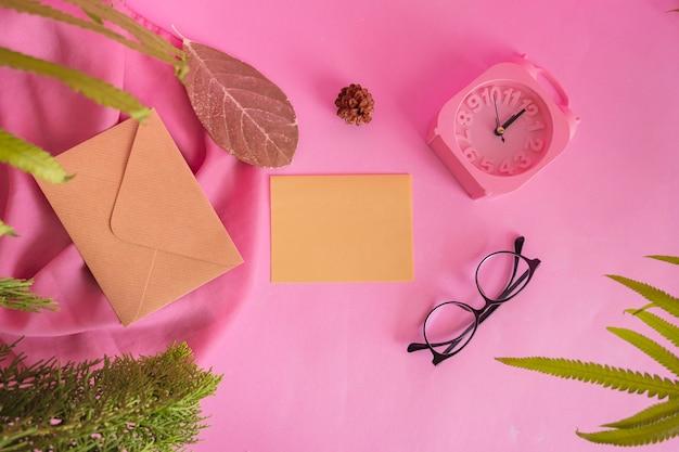 제품을 특징으로 하는 구성 아이디어의 개념. 안경, 시계, 소나무 꽃, 잎, 천으로 장식된 분홍색 배경의 연하장