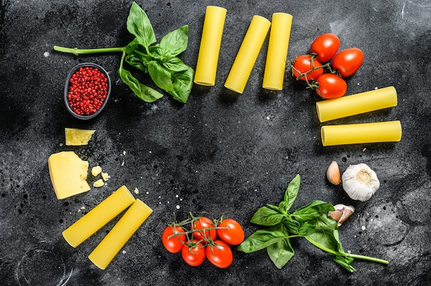 Концепция приготовления пасты каннеллони. ингредиенты базилик, помидоры черри, пармезан, чеснок. вид сверху. копировать пространство
