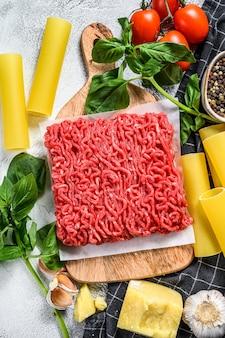 Концепция приготовления пасты каннеллони с говяжьим фаршем. ингредиенты базилик, помидоры черри, пармезан, чеснок. серый фон вид сверху