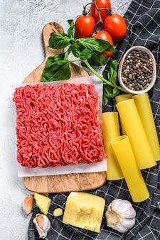 Концепция приготовления пасты каннеллони с говяжьим фаршем. ингредиенты базилик, помидоры черри, пармезан, чеснок