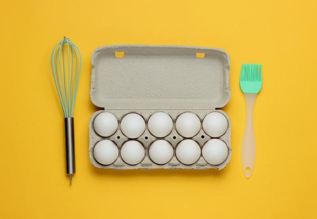 黄色の背景に卵キッチンツール泡立て器ブラシの段ボールトレイを調理するの概念