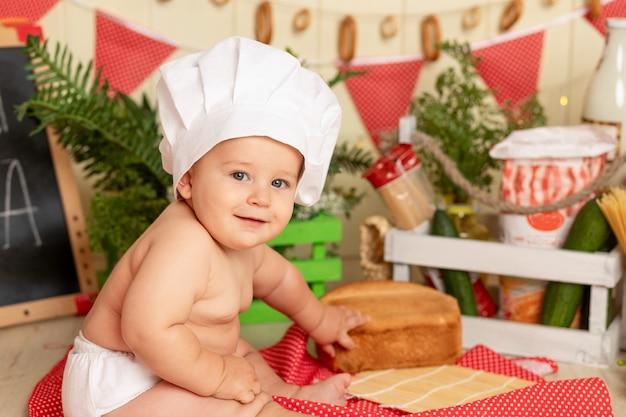 料理のコンセプト、パンと一緒にキッチンに座っているシェフの帽子をかぶった幸せな小さな子供