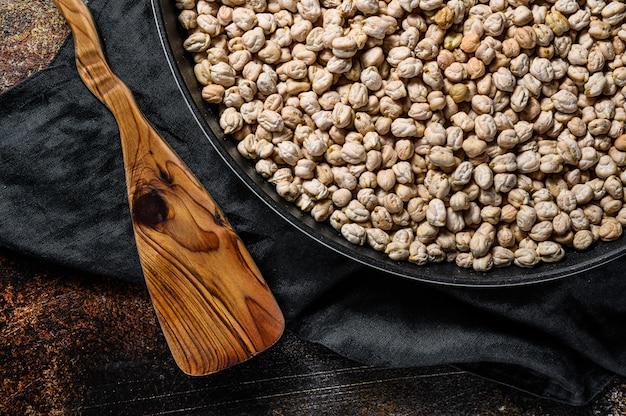 ローストヒヨコ豆をピンクコショウで調理する概念。健康的なベジタリアン料理。暗い背景。上面図