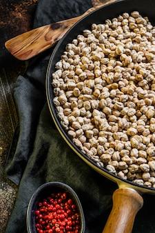 ピンクペッパーでひよこ豆のローストを調理するコンセプト。健康的なベジタリアン料理。暗い背景。上面図