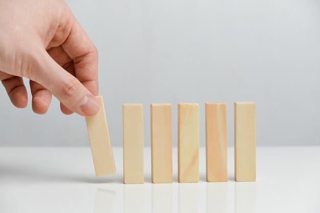 Концепция создания поэтапного бизнеса. рука держит деревянные блоки на белом пространстве.