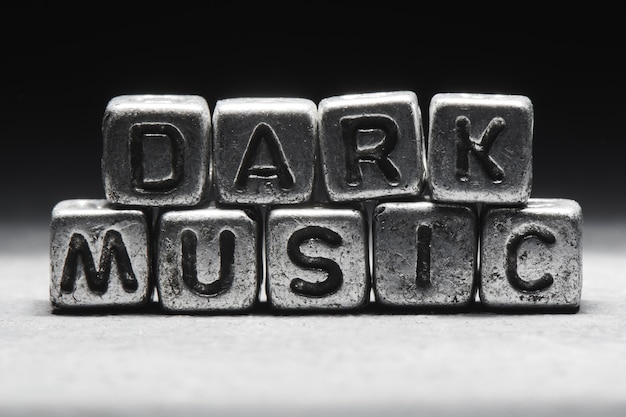 ダークミュージックのコンセプト。黒の背景、グランジスタイルで分離された金属3dキューブの碑文
