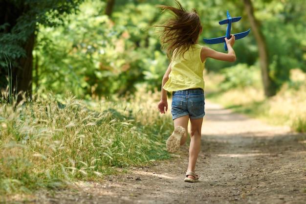 夢と旅行のコンセプト。自然の夏におもちゃの飛行機で遊んで幸せな女の子子供。