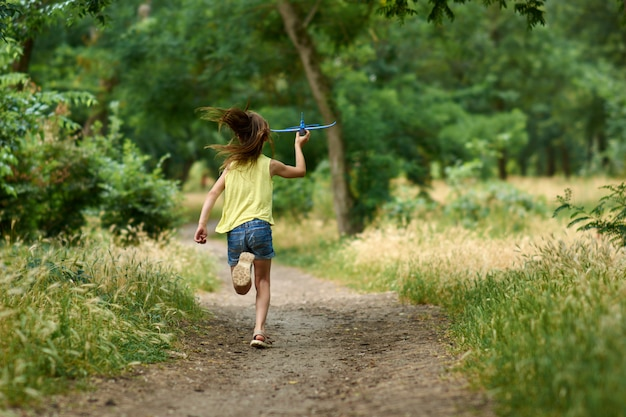 Концепция мечты и путешествия. счастливая девушка ребенок играет с игрушкой самолет летом на природе.