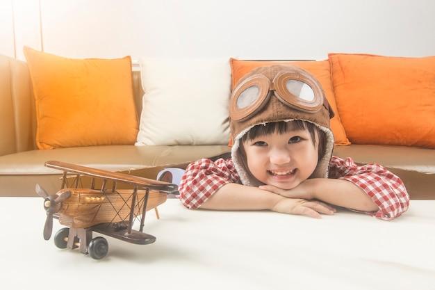 夢と旅行の概念。子供はパイロットの役割を果たし、宇宙に飛ぶことを夢見ています。