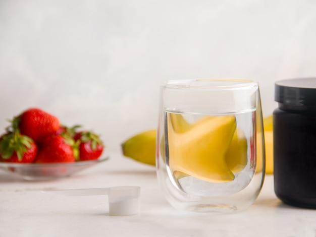 스포츠에 관련된 사람들에게 유용한 음료의 개념. 과일 옆에 강화 음료